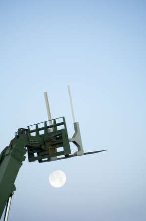 Boom lift with rising moon photo