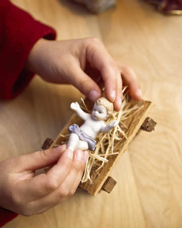 bodypart: Child playing with figure of baby Jesus