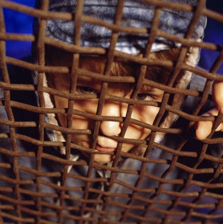 frightfulness: Child looking through rusty gate
