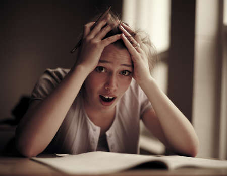 burdened: Anxious woman studying