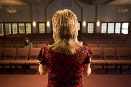 hablar en publico: Mujer al frente de una habitaci�n vac�a  Foto de archivo