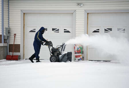 snow clearing: Man operating a snow blower