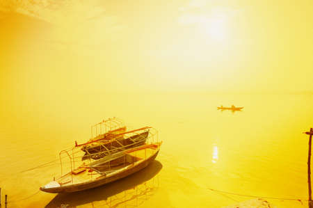 monotone holy: Sun shining on a boat on the Ganges river, India Stock Photo