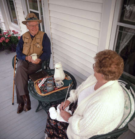 seventy something: Couple on the porch Stock Photo