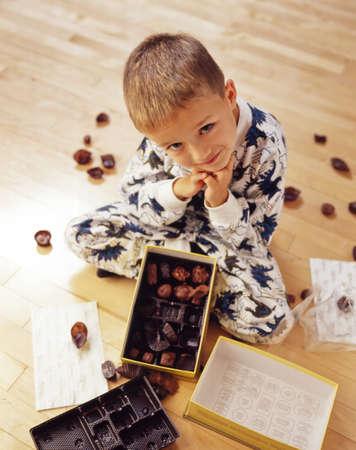 mischievous: Boy into box of chocolates Stock Photo