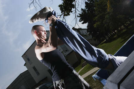 antagonistic: Man holding a person by the legs Stock Photo