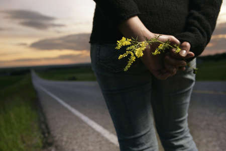 bodypart: Woman standing at the side of the road with wild flowers