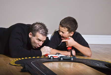 Father and son playing with race track Stock Photo