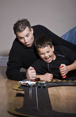 Father and son playing with race track Stock Photo - 7208255