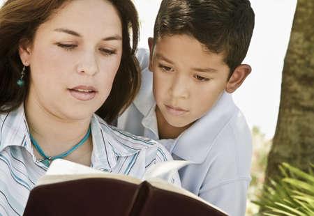 belief systems: Madre e figlio leggendo una Bibbia