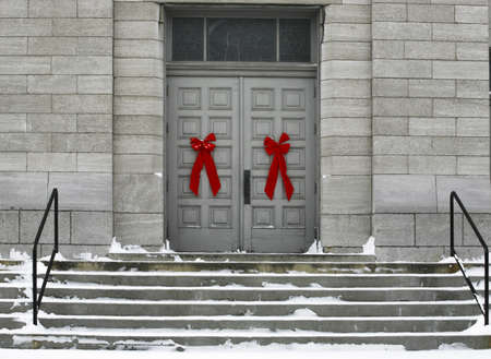 fullframes: Red bows on doors of a grey building