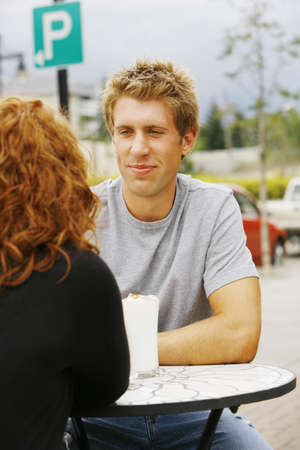 Man looking at woman at outdoor cafe photo