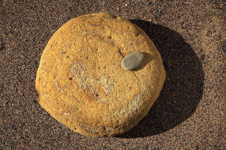 Large and small stone on sand