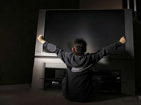 Child sitting in front of television Stock Photo - 7208530
