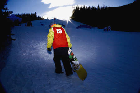 wintersport: Snowboarder climbing up ski hill,Kananaskis,Alberta,Canada Stock Photo