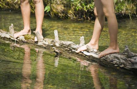 bodypart: Children standing on a log in a stream
