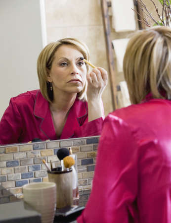 50 something fifty something: Woman applying makeup Stock Photo