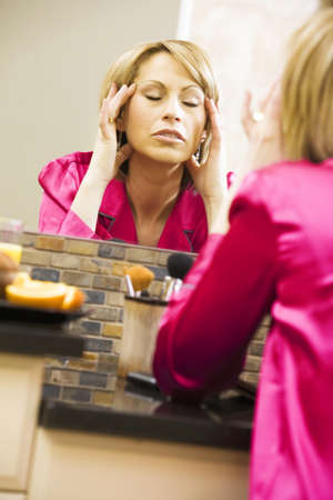 50 something fifty something: Woman massaging her head in mirror Stock Photo