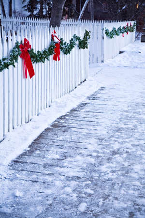decoration: Christmas garland and red bows on a white picket fence Stock Photo