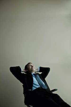 50 something: Businessman reclining in chair Stock Photo