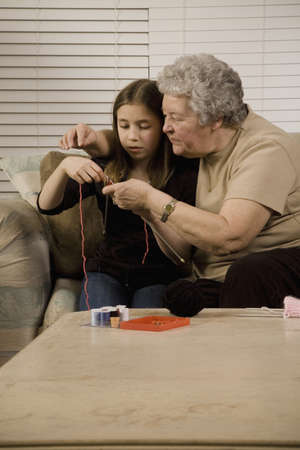 family unit: Grandmother and granddaughter knitting
