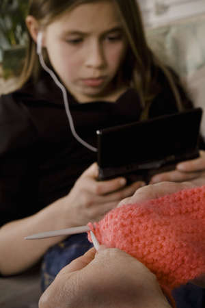 Girl with earbuds in and another person knitting photo