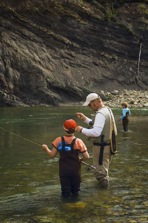 instructing: Father and sons fly fishing in mountain river