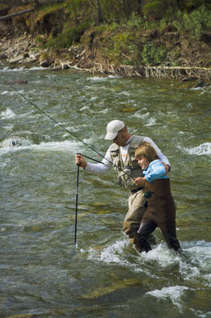 50 something: Father and son crossing a mountain fly fishing river   Stock Photo
