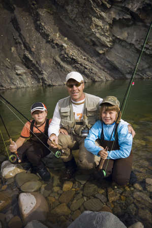 Father and sons in a mountain fly fishing river,Nordegg,Alberta,Canada