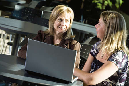 acquaintance: Two women working on a laptop Stock Photo