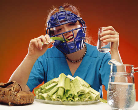 Women wearing sports equipment eating celery photo