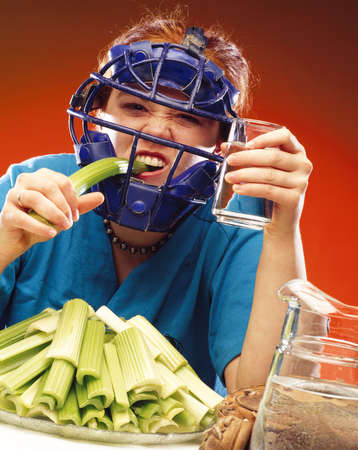 Woman in sports equipment eating celery photo