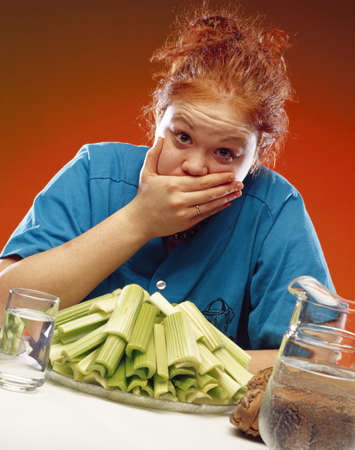 bulimia: Woman with plate of celery and sports equipment