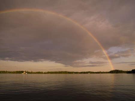 atmospheric phenomena: Lake of the woods,Ontario,Canada,Rainbow over the lake Stock Photo
