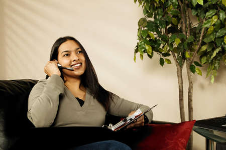 earpiece: A woman working at home Stock Photo