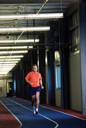 50 something fifty something: Man running on an indoor track Stock Photo