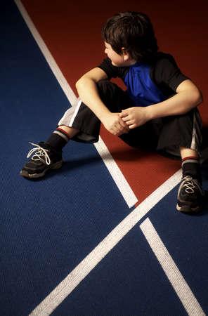 race track: Boy sitting on a race track Stock Photo