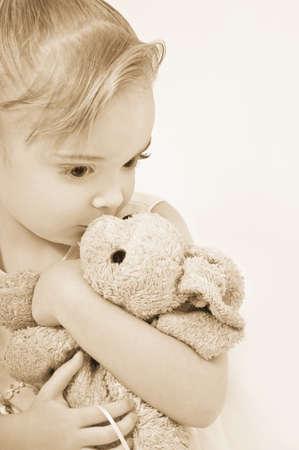 sepias: Girl kissing her stuffed animal