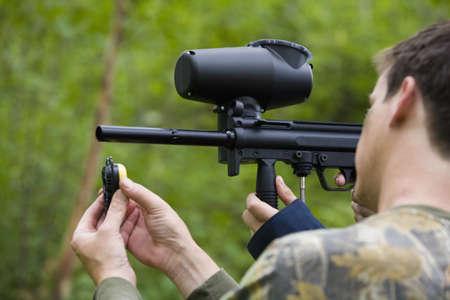 antagonistic: Man loading paintball gun
