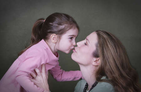Mother and daughter kissing photo