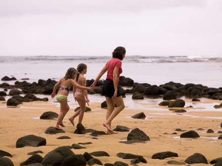 30 something women: Walking along a beach in Kauai, Hawaii, USA