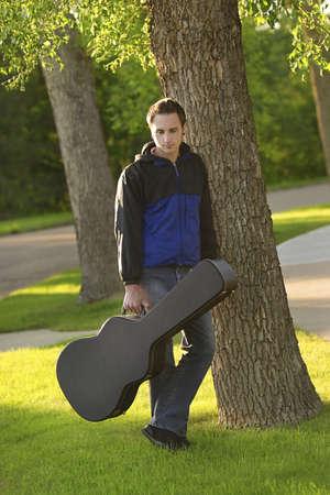 guitar case: Hombre que plantea con su caso de guitarra