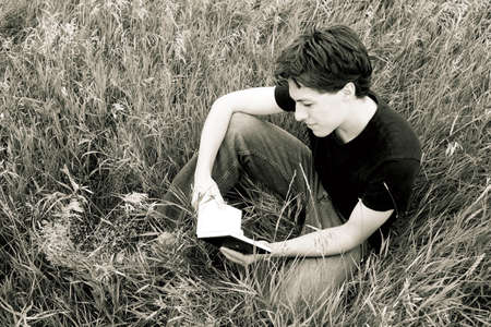 scripture: Man reading in the grass Stock Photo