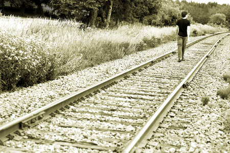 contented: Man walking on train tracks