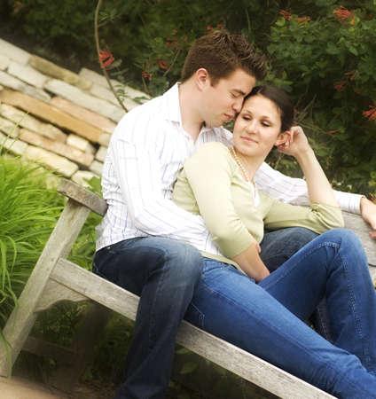 pareja abrazada: Pareja sentada en un Banco
