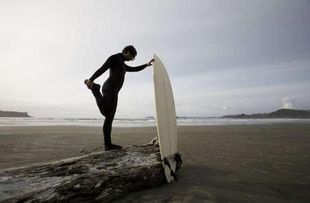 Surfer uitrekken op strand Stockfoto