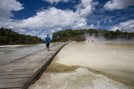Man at geothermal site, Wai-O-Tapu Thermal Wonderland on North Island of New Zealand
