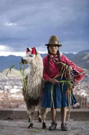 lama: Peruvian woman with her llama (Lama glama), Cuzco, Peru