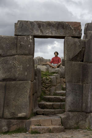 incan: A young man meditates in ancient Incan ruins outside Cuzco, Peru Stock Photo
