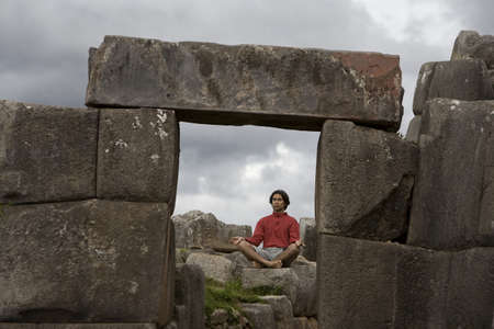 A young man meditates in ancient Incan ruins outside Cuzco, Peru photo